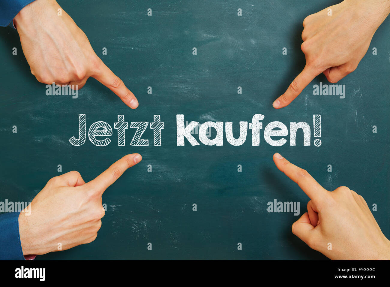 hands pointing to German slogan 'Jetzt kaufen!' (buy now!) on a chalkboard - Stock Image