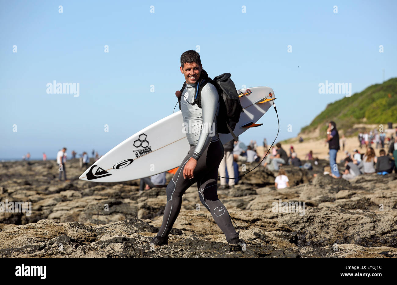 Big wave surfer and WSL commentator Peter Mel walks to the surf for water commentary at the 2015 J Bay Open - Stock Image