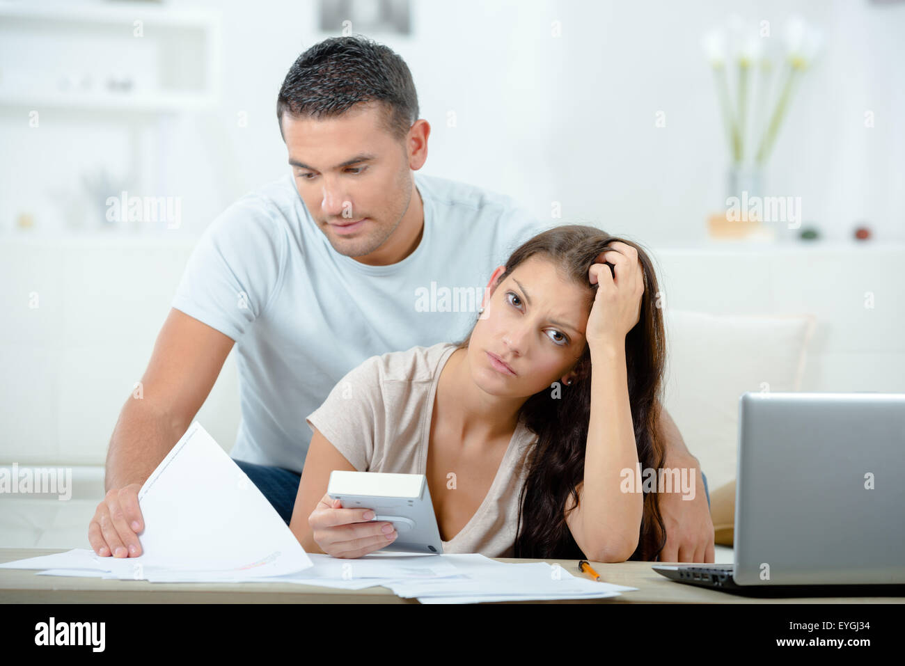 Couple with papers, calculator and computer - Stock Image