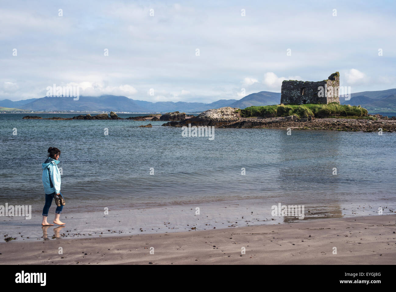 Woman walking on beach with Ballinskelligs Castle in background; County Kerry, Ireland, UK - Stock Image
