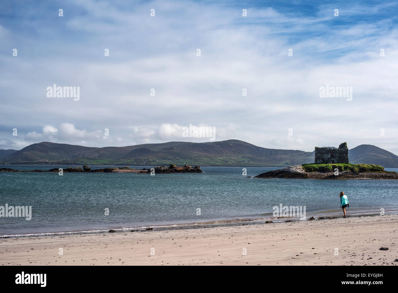 UK, Ireland, County Kerry, Woman walking on beach with Ballinskelligs Castle in background - Stock Image