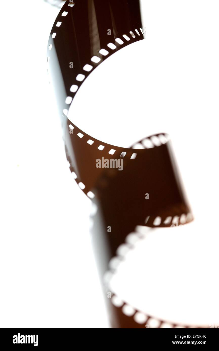 A twirled 35mm negative film strip on a light box in processing lab Stock Photo