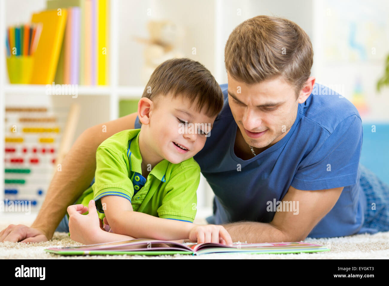 Father and son read together sitting on the floor. Kid reading story book with his dad at home. - Stock Image