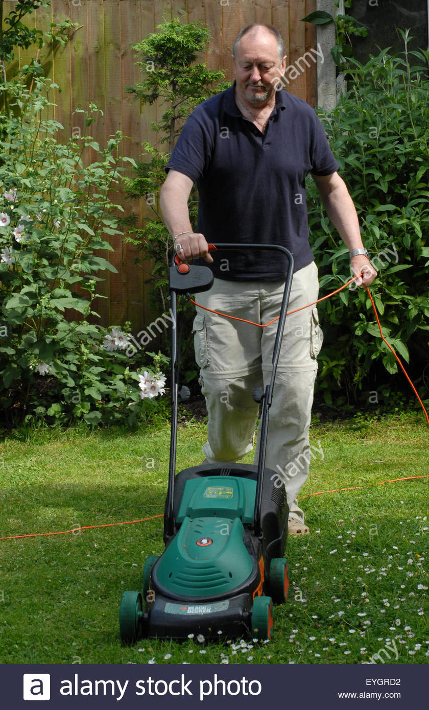 man mowing lawn - Stock Image