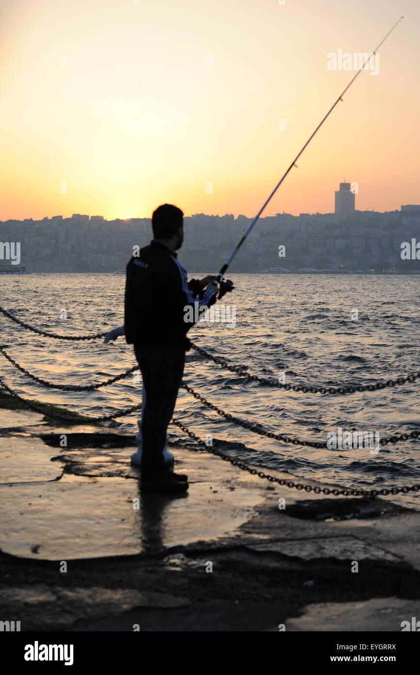 Fisherman in sunset at Üsküdar pier at Bosporus in Istanbul Turkey - Stock Image