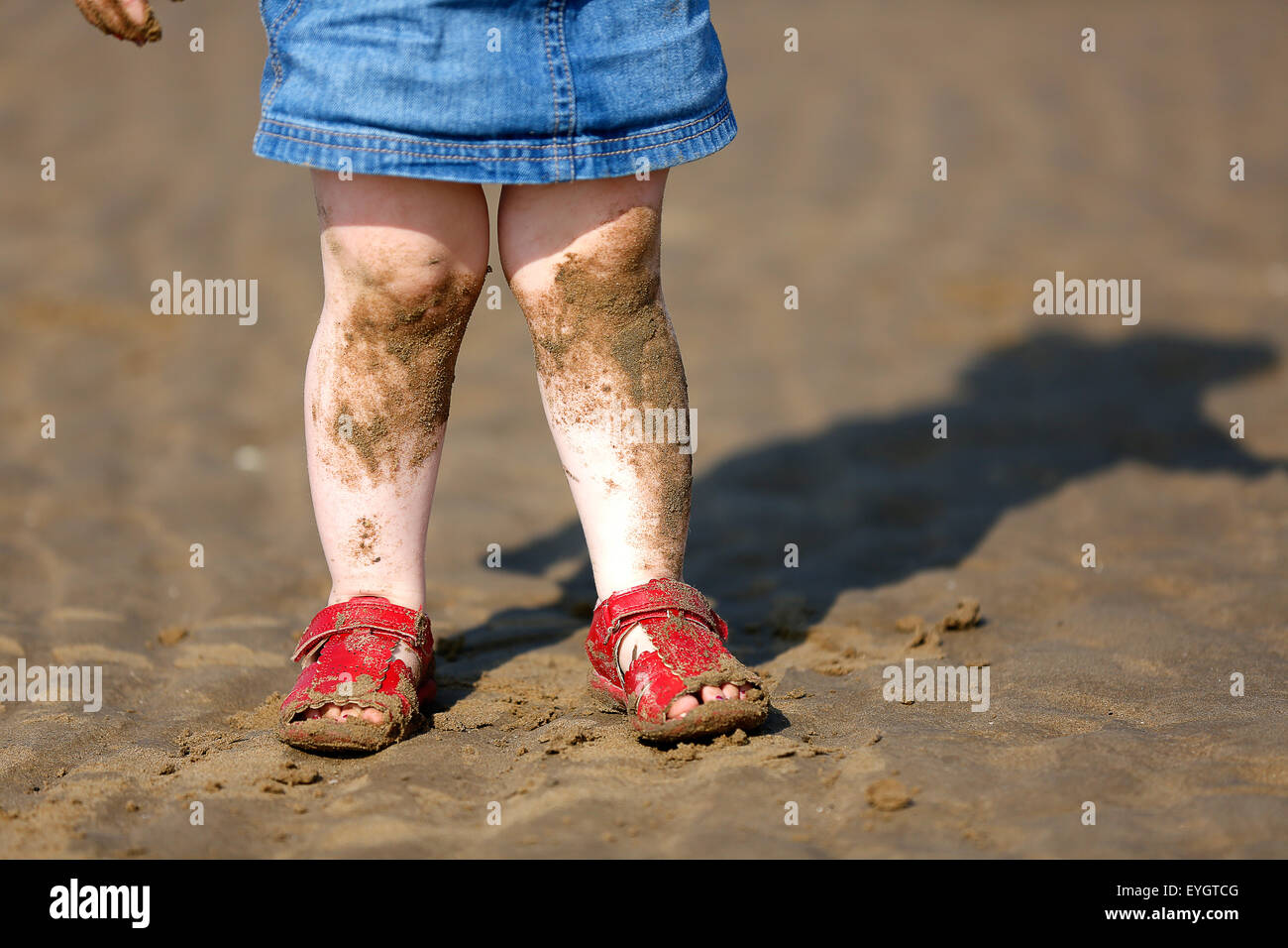 A young female child standing on an English beach. She has sand covered legs from where she  has been playing nad - Stock Image
