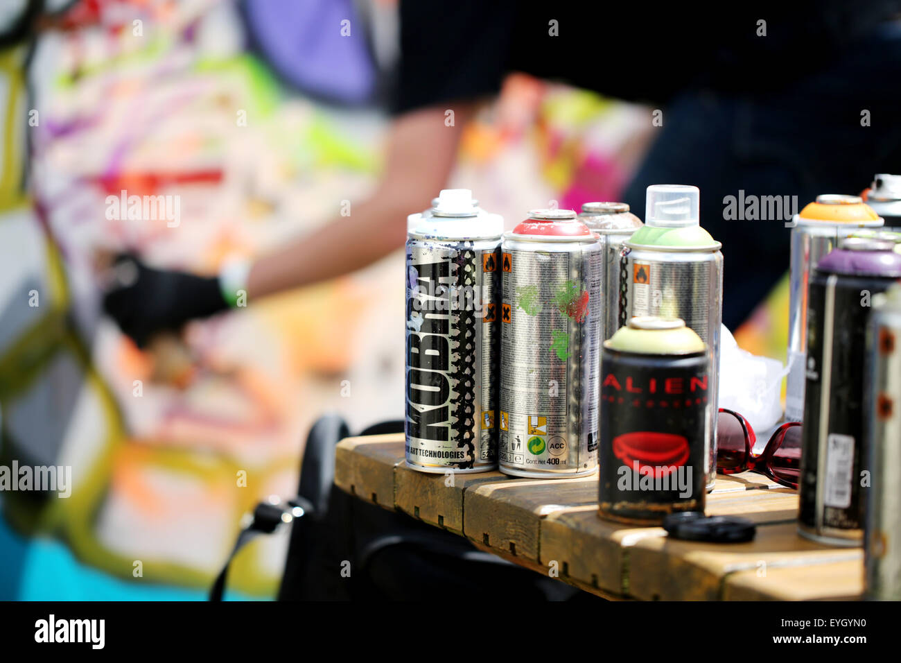 A group of used Kobra graffiti artists spray cans left on a table at the Bristol Upfest event. A blurred working Stock Photo