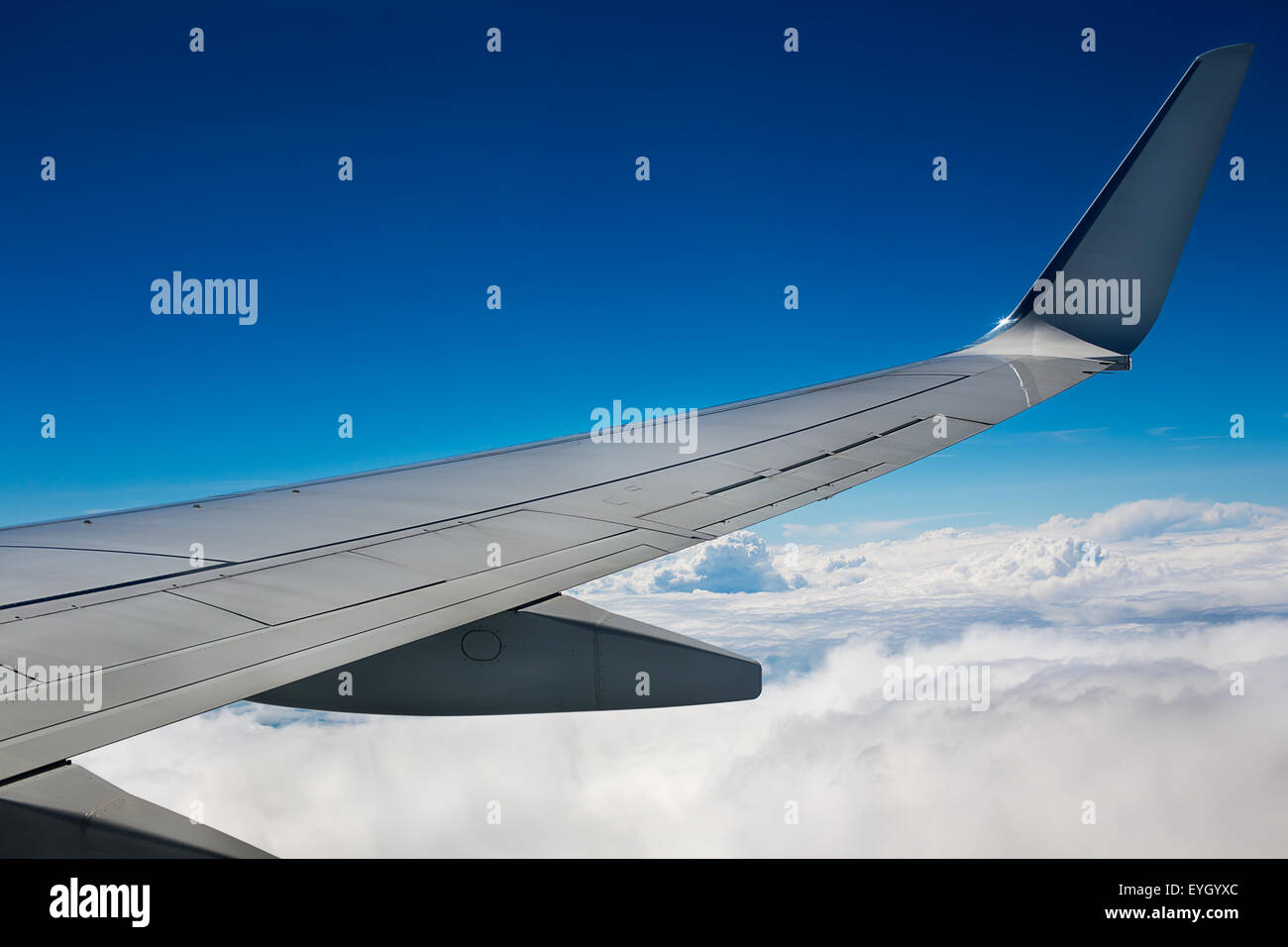 Airplane wing on sky and clouds background - Stock Image