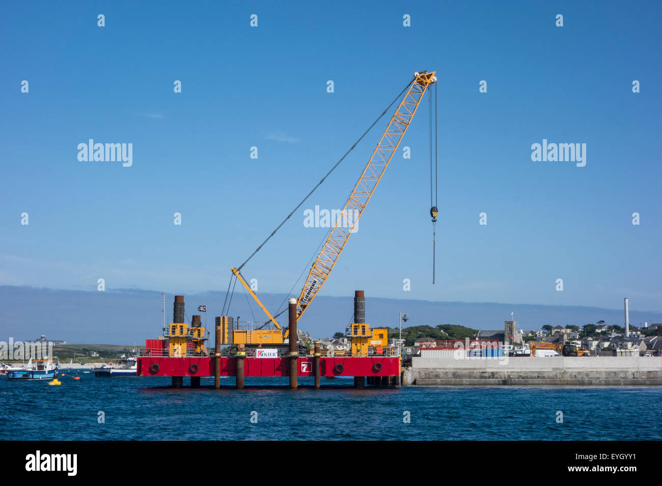 Construction work, involving a crane, to lengthen the harbour wall on St Mary's, Isles of Scilly, Cornwall - Stock Image