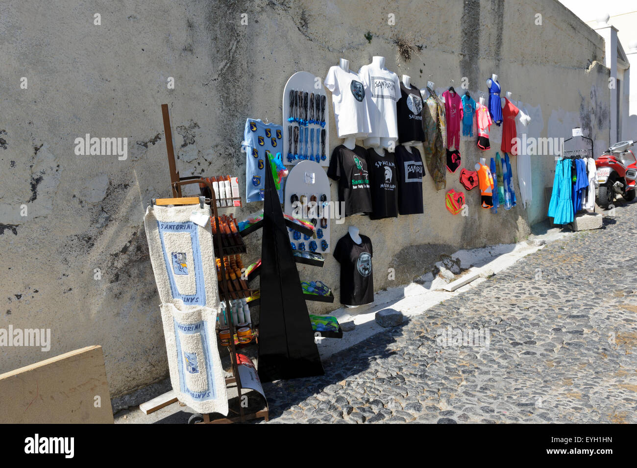 Clothes for sale in a narrow cobbled street in Fira, Santorini, Greece. - Stock Image