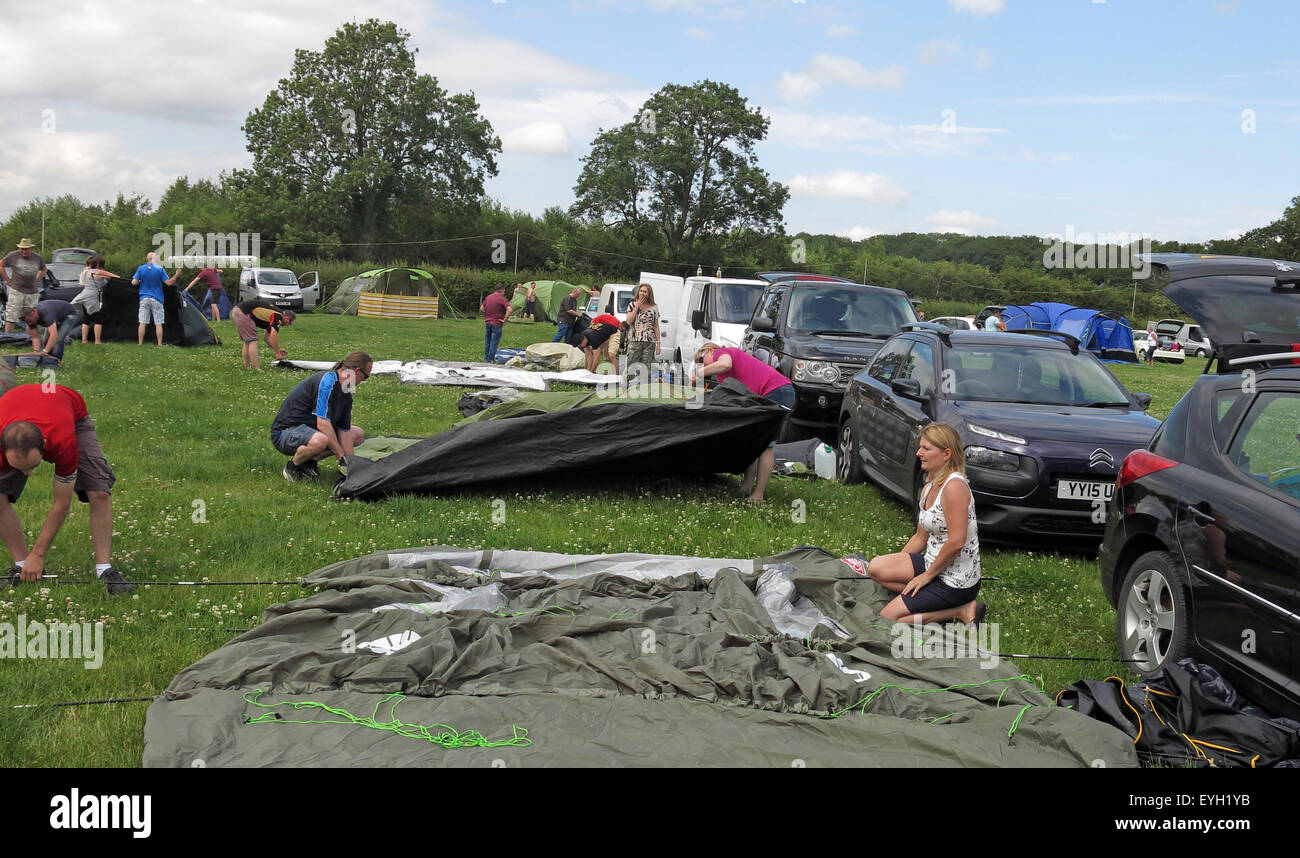 Random people putting up tents in a field - Stock Image