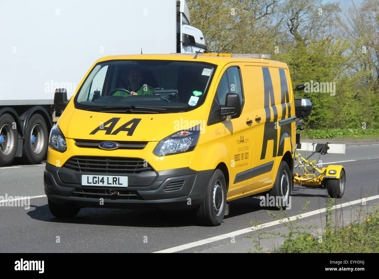 A 2014 AA BREAKDOWN RESCUE YELLOW VAN DRIVING ALONG A MAIN A ROAD WITH A TRAILER CARRYING A MOTORCYCLE - Stock Image
