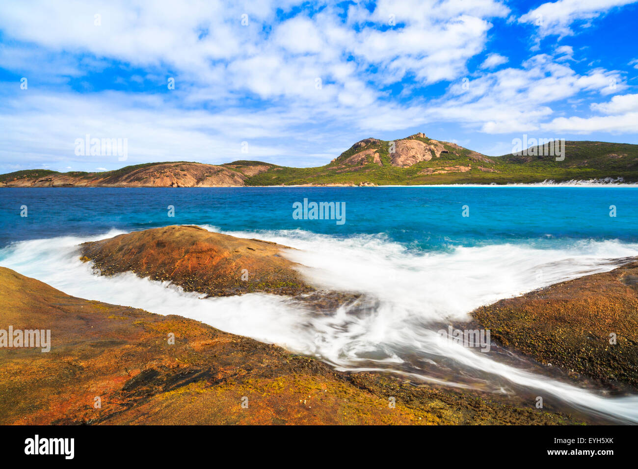 A wave pouring over granite rocks at Thistle Cove in Cape Le Grand National Park, near Esperance, Western Australia - Stock Image
