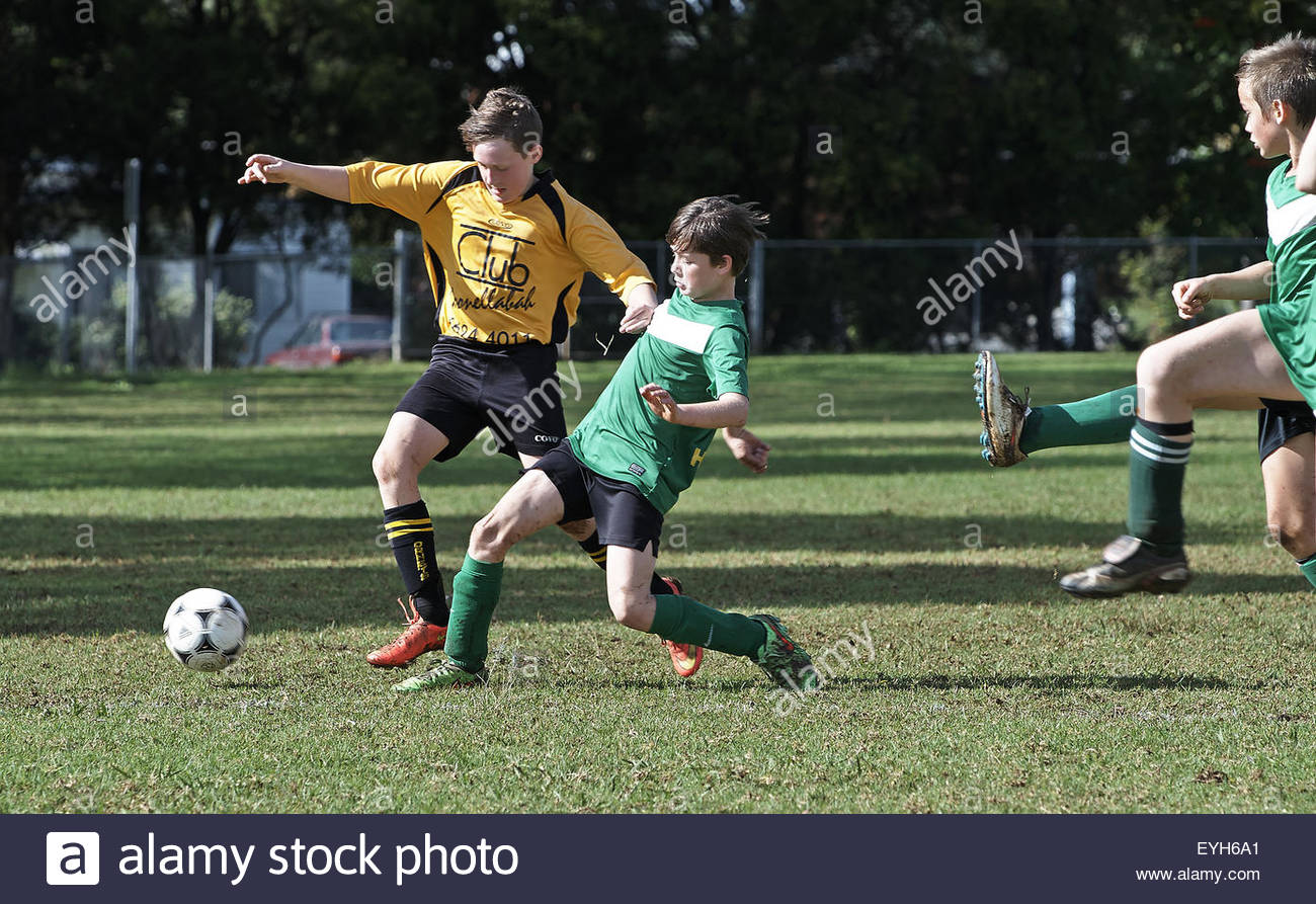 Young male football players compete for possession of the ball, during a weekend match between Goonellabah and Nimbin - Stock Image