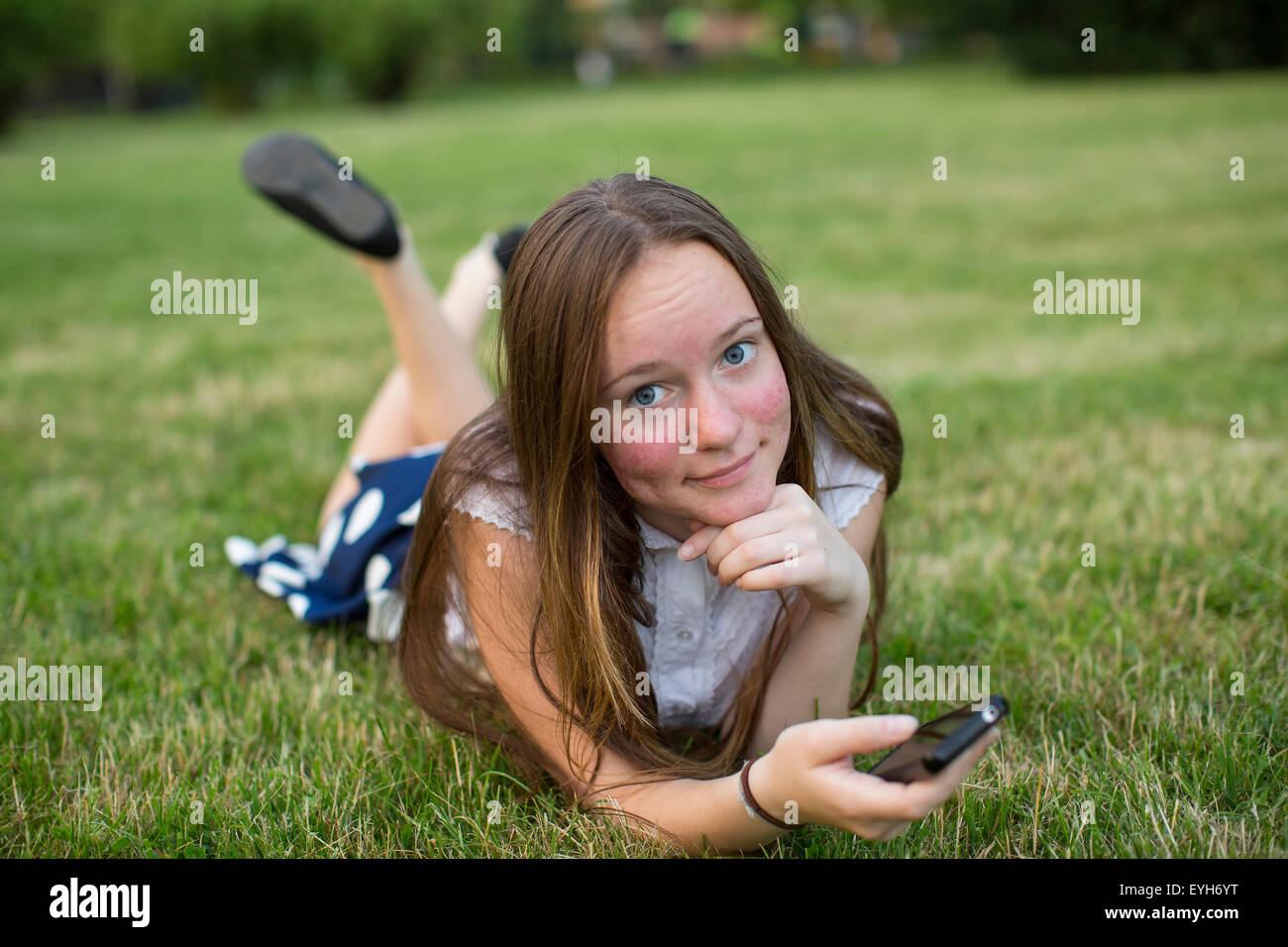 cute teen girl with a smartphone in hands of lying on green grass stock photo 85815852 alamy - Cute Teen Com