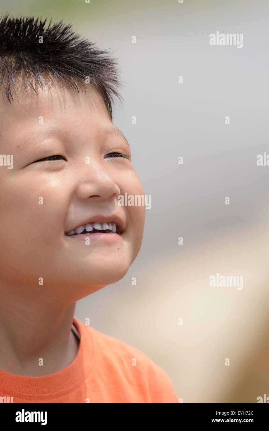 Portrait of a little mongoloid boy happy and smiling with copy space - Stock Image