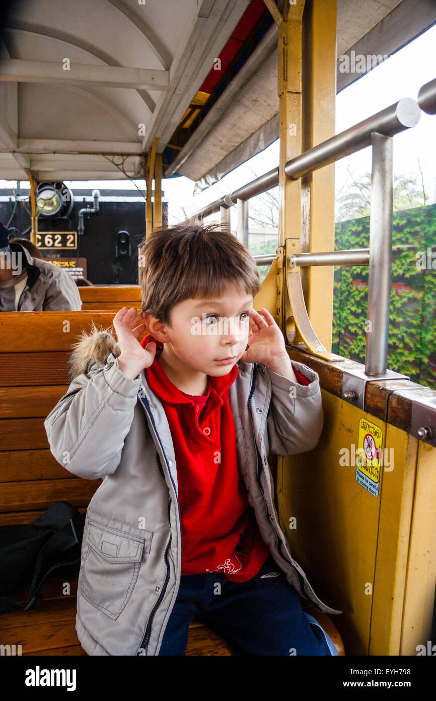 4 to 6 year old Caucasian boy sitting on open train looking out with hands around both ears, very angelic - Stock Image
