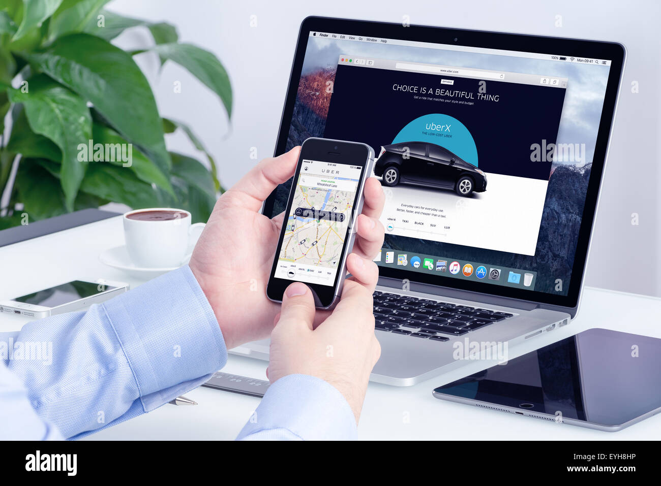 Varna, Bulgaria - May 29, 2015: Man orders Uber X through his iPhone and Macbook with Uber website on the background. Stock Photo
