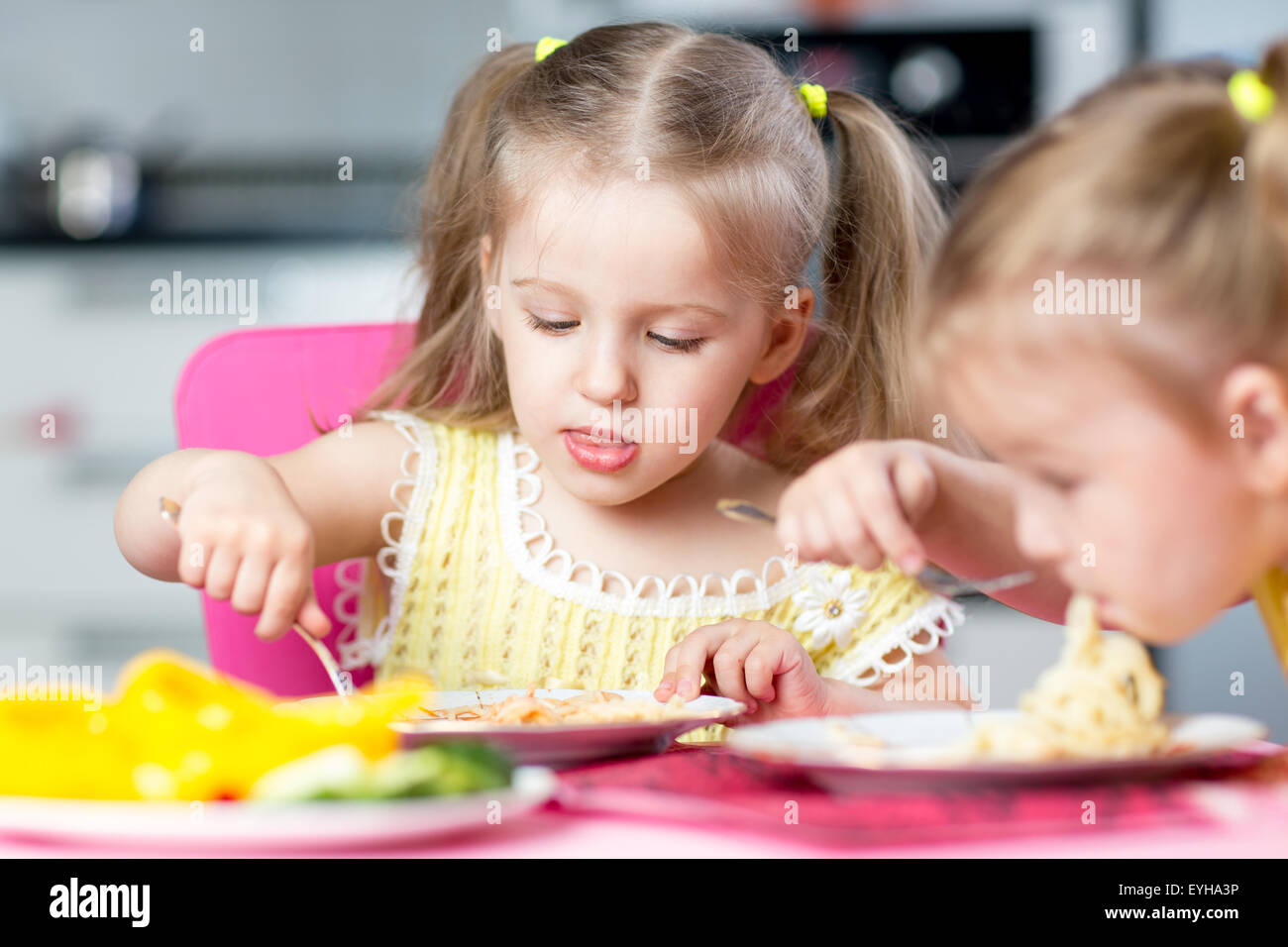 Kids eating spaghetti with vegetables in nursery - Stock Image