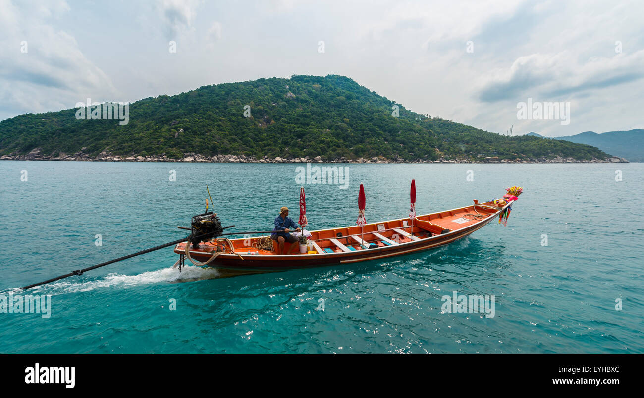 Thai man steering a longtail boat, island of Koh Tao, Gulf of Thailand, Thailand - Stock Image