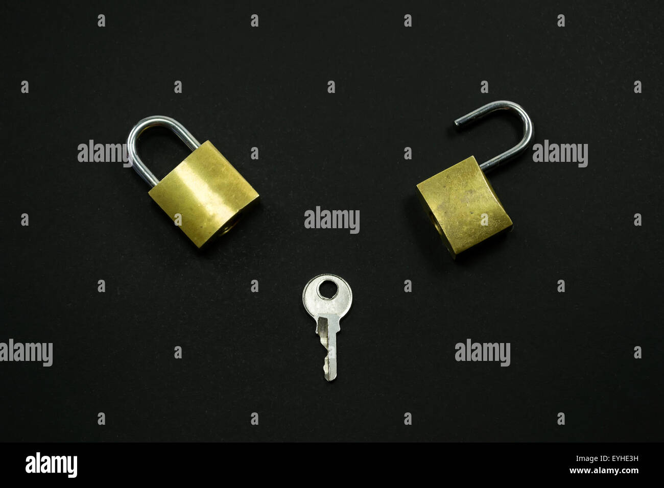 Two small locks and a key against a black background , conceptual image about problem solving process - Stock Image