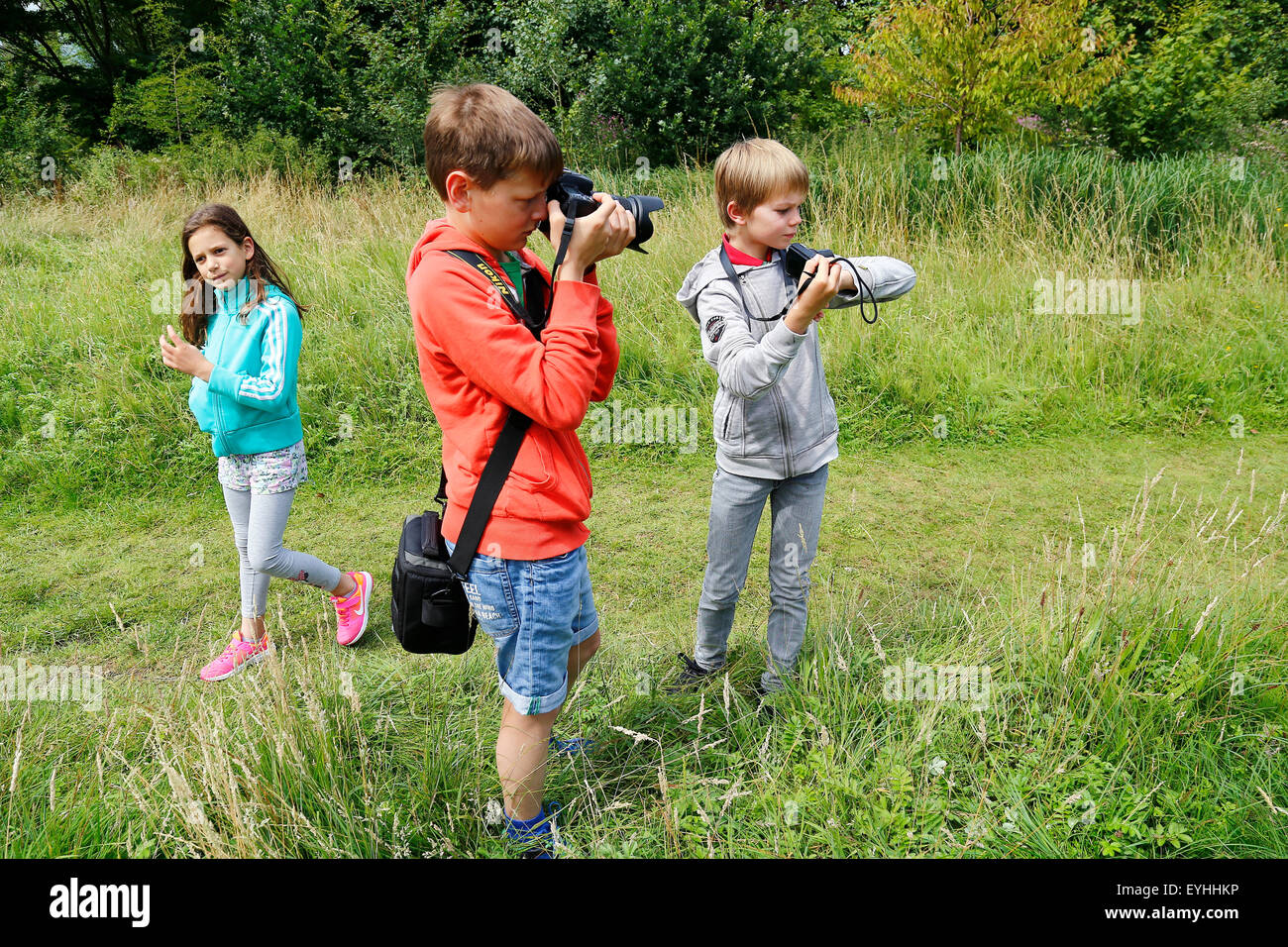 children taking a picture on a grasshopper on boy's arm - Stock Image