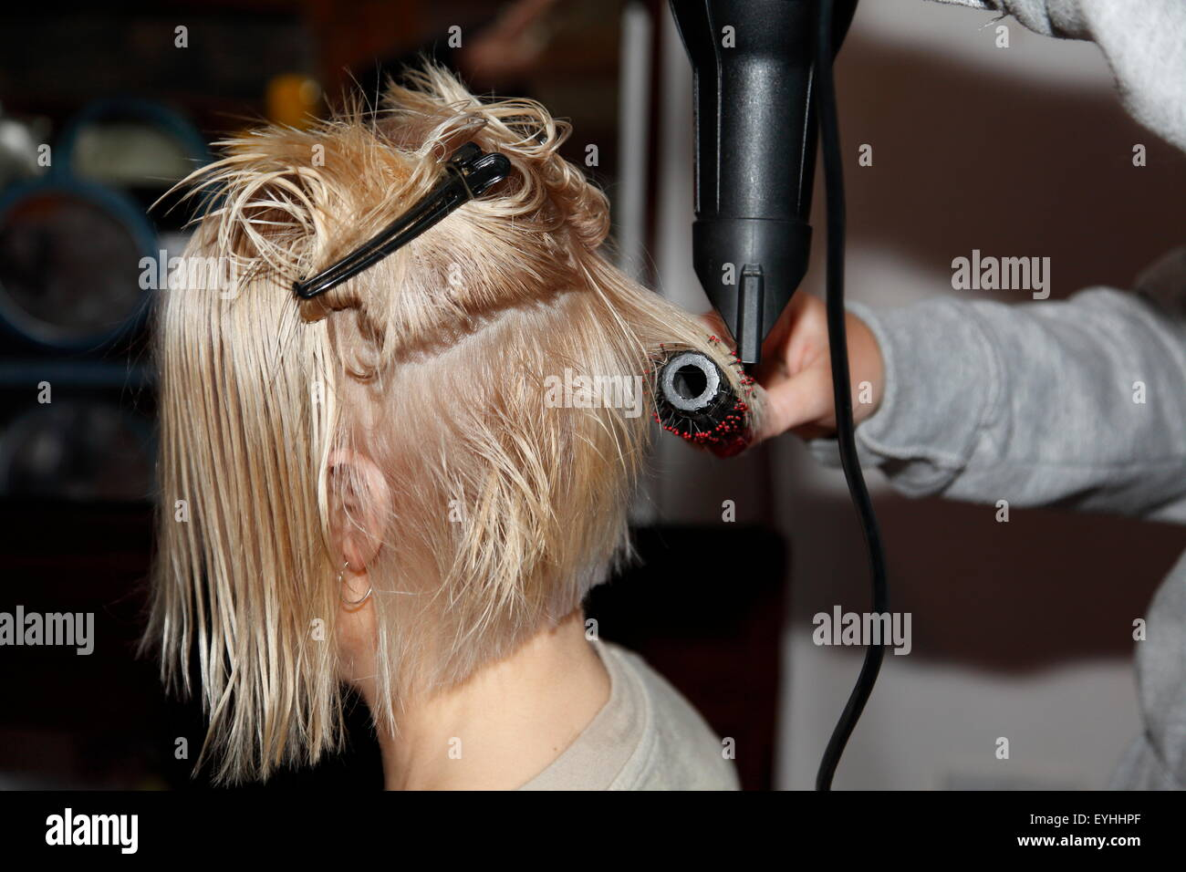 Woman receiving a haircut in her home in Oldham, UK - Stock Image