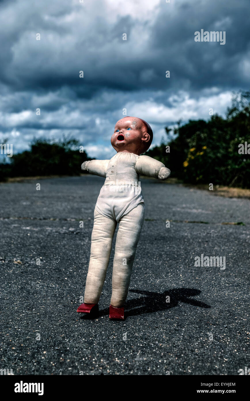 a damaged vintage doll, just about to fall - Stock Image