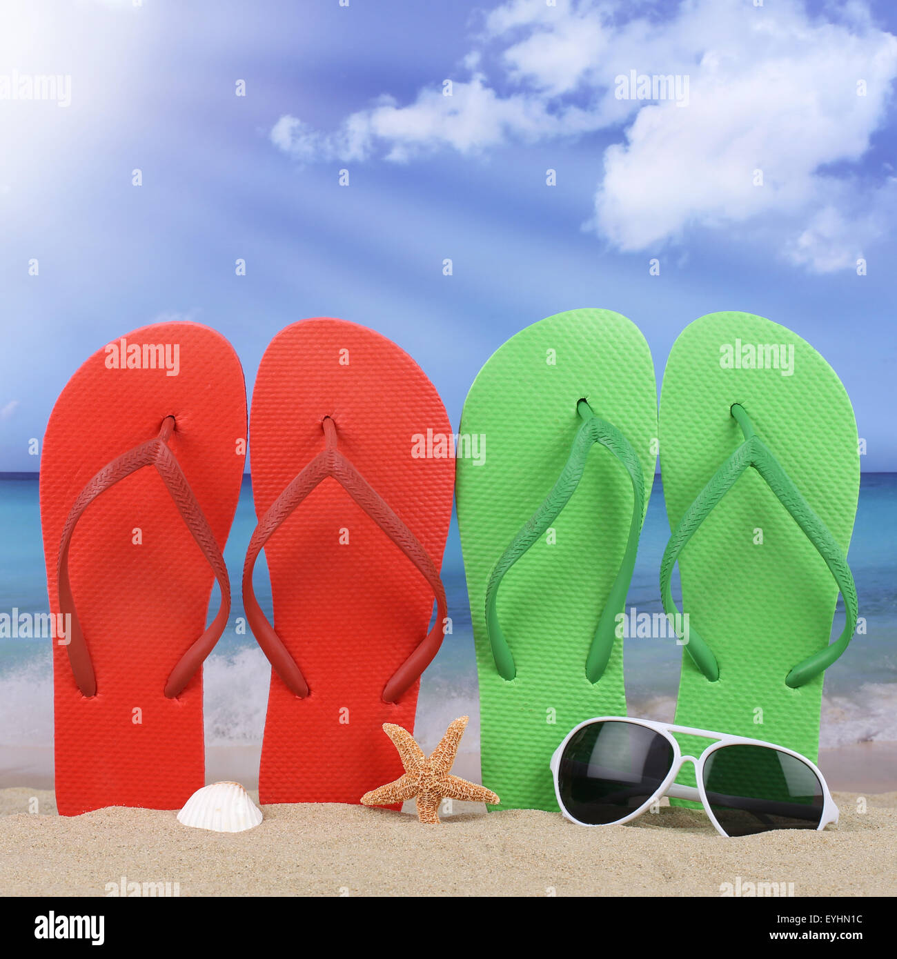 Beach scene with flip flops sandals sun in summer on vacation - Stock Image