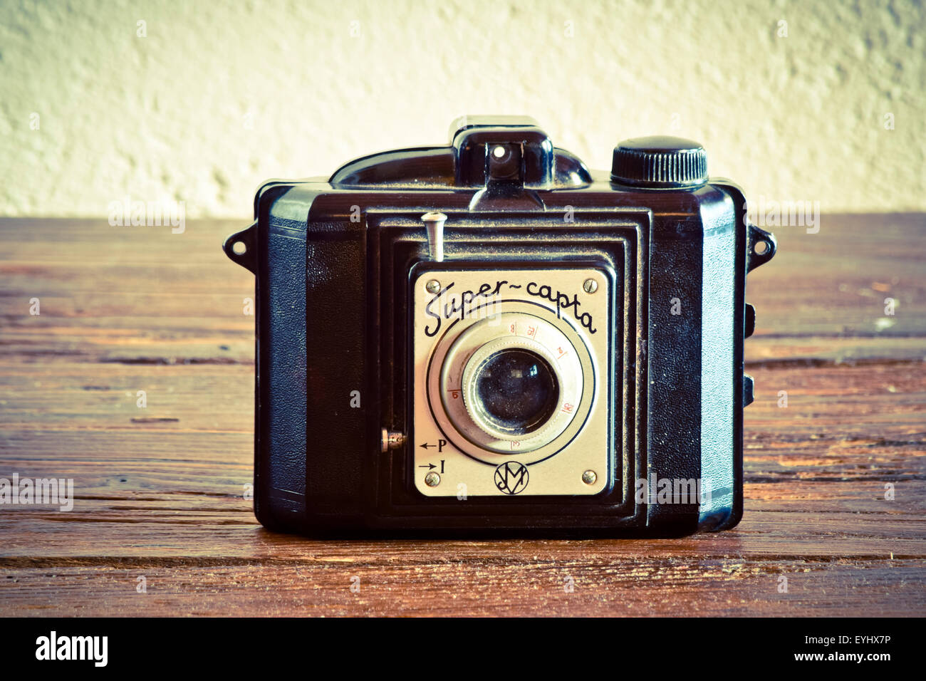 Old camera on wooden surface. - Stock Image