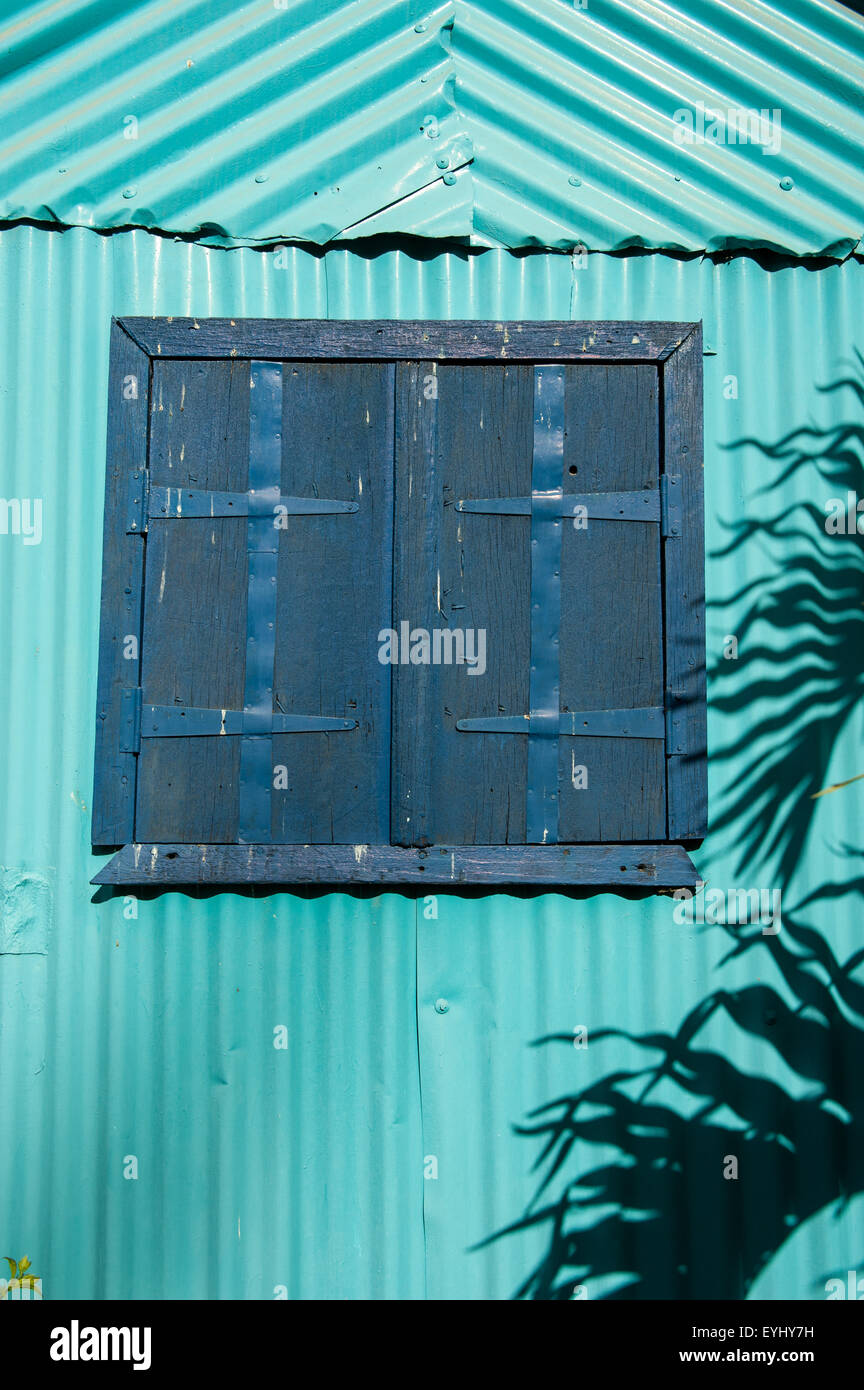 Flic en Flac, Mauritius. Closed blue shutters on a tourquoise corrugated wall with palm leaf shadow. - Stock Image