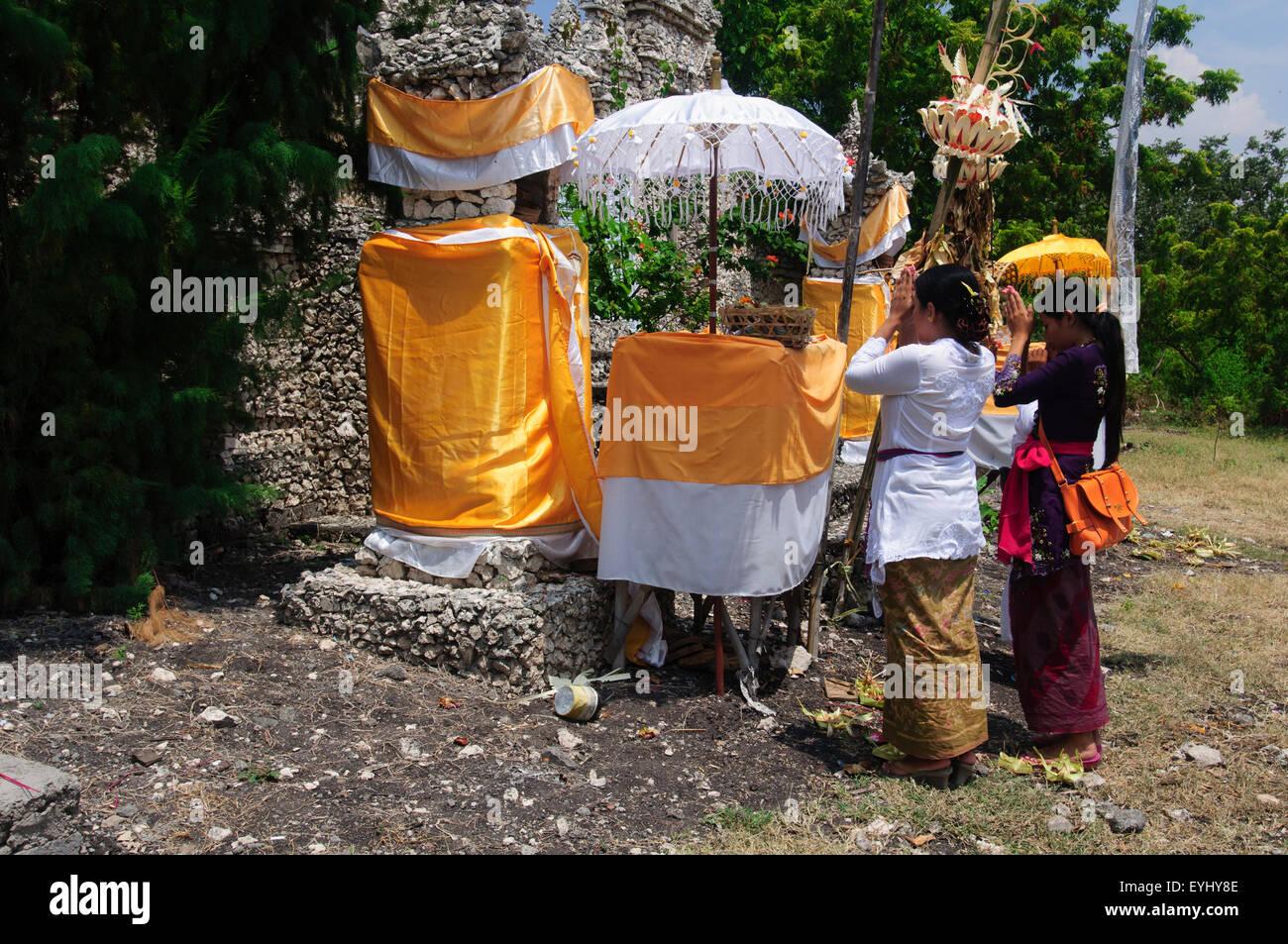 Two women praying at a Hindu Temple at the island of Menjangan in West Bali National Park, Bali, Indonesia - Stock Image