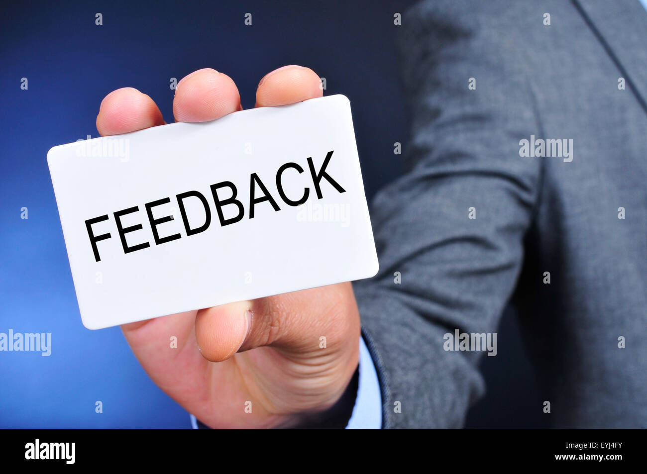 closeup of a young caucasian man in suit showing a signboard with the word feedback written in it - Stock Image