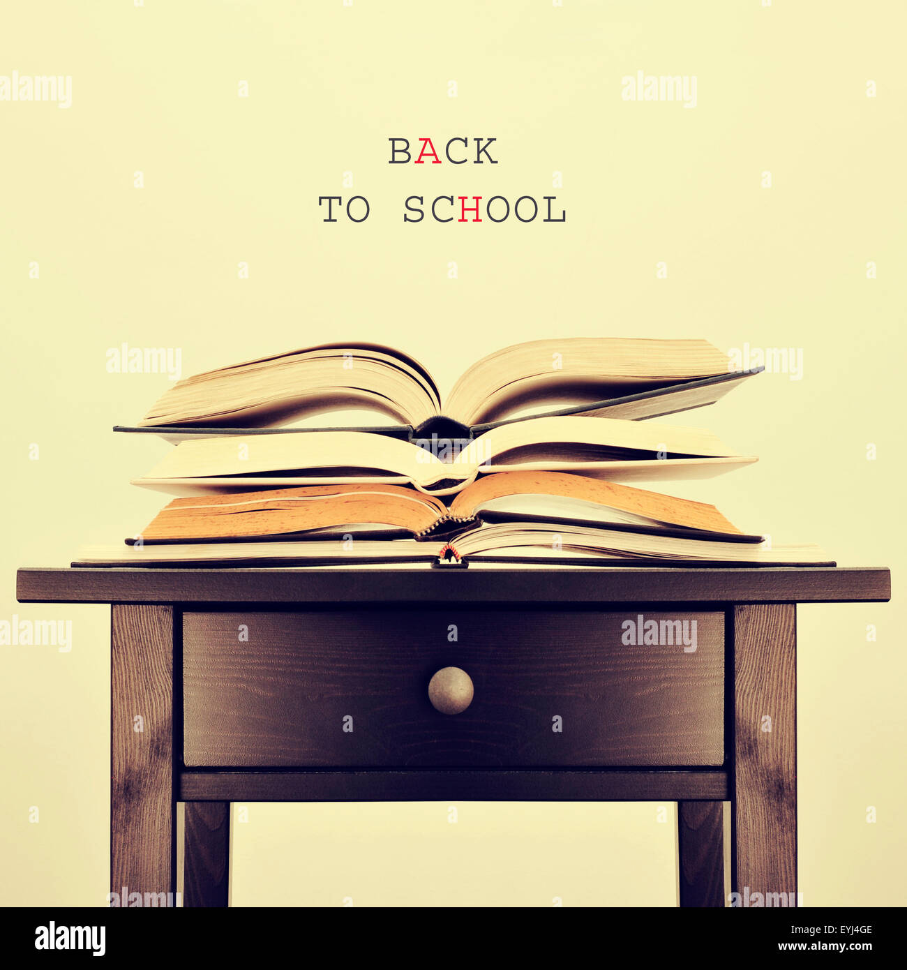 some open books on a table and the sentence back to school on a beige background, with a retro effect - Stock Image