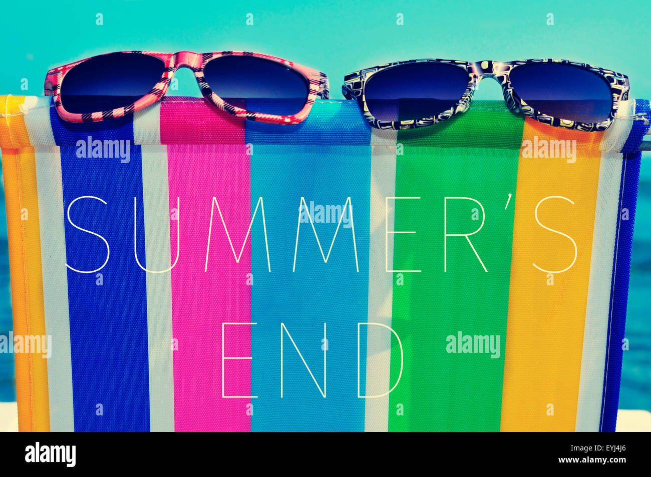 a pair of sunglasses on a colorful deck chair and the text summers end - Stock Image