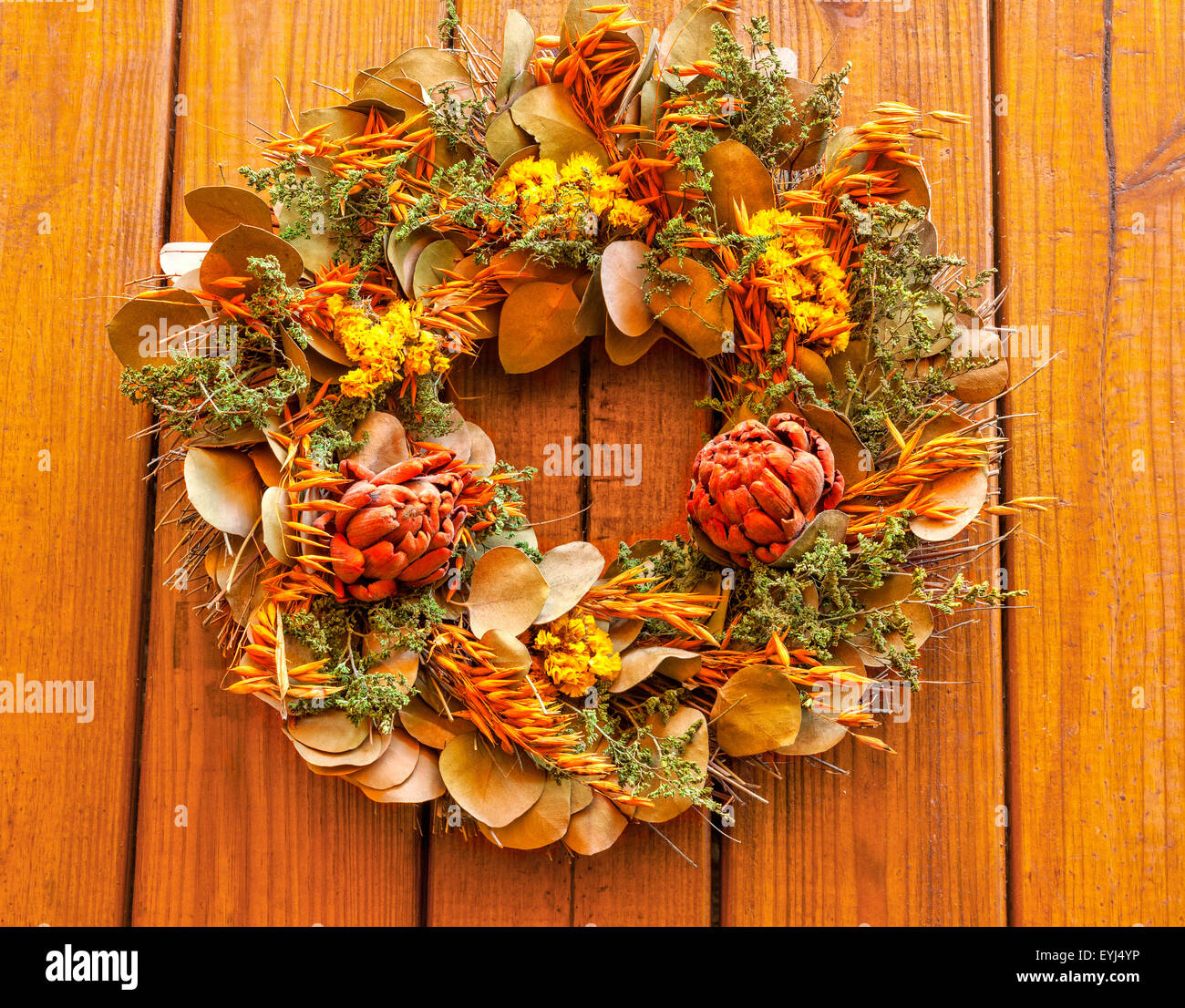 Autumn wreath with dried flowers against a wooden background Stock Photo