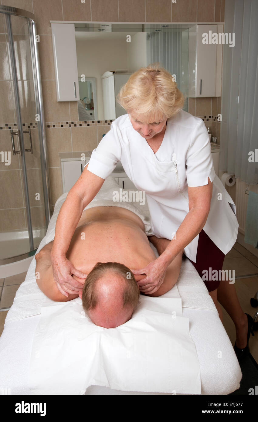 Masseuse working with a male client Providing a relaxing back massage Stock Photo