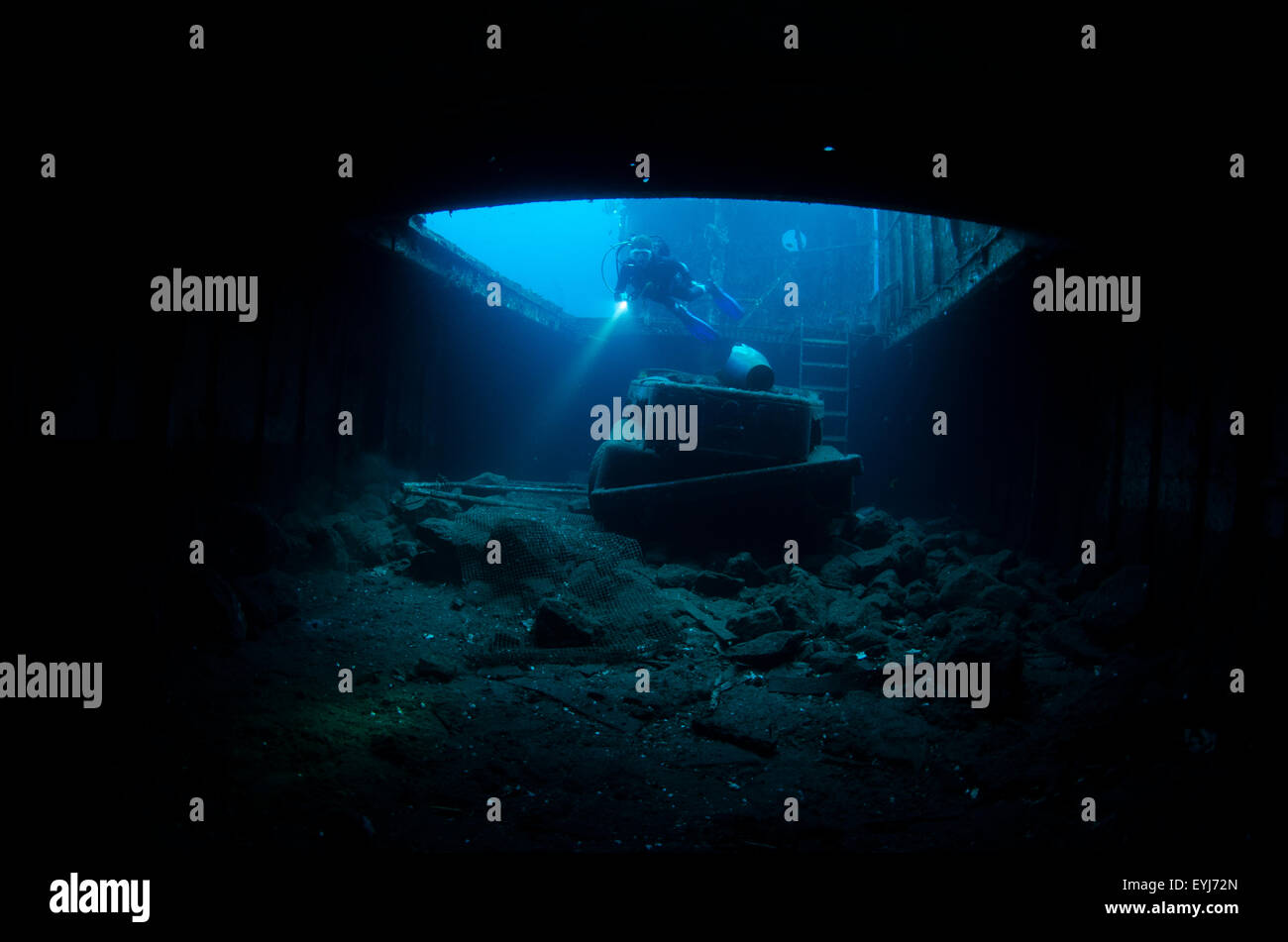 A diver descends into the hull of the purposefully sunk artificial reef known as the Kubu Shipwreck in Tulamben, - Stock Image
