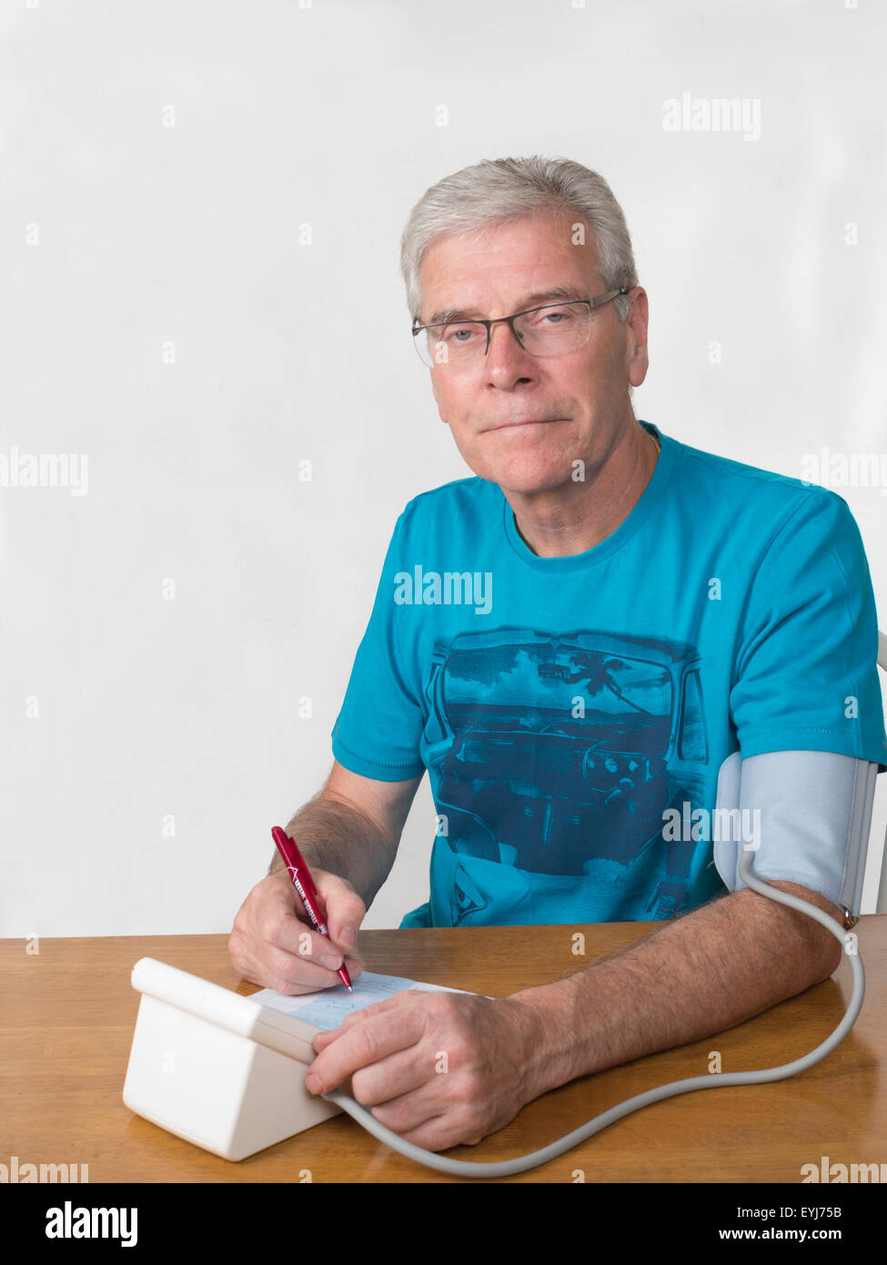 Middle aged man taking blood pressure readings white background looking towards camera vertical shot and looking - Stock Image