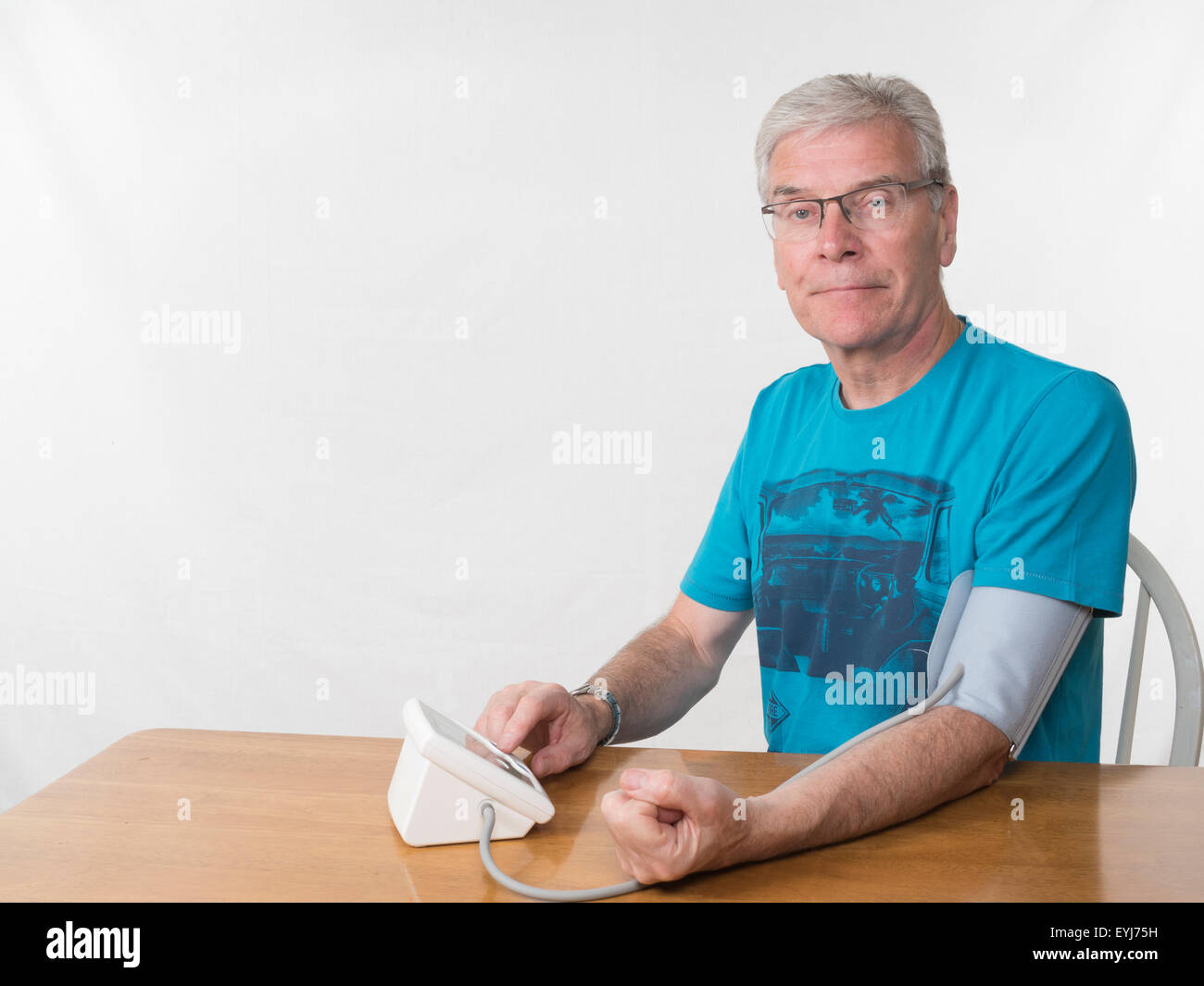 Middle aged man taking blood pressure readings white background looking towards camera - Stock Image