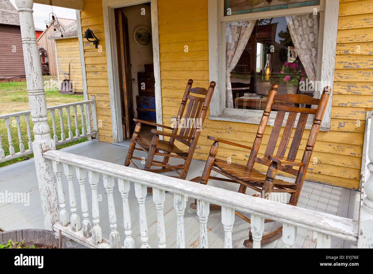 A pair of old wooden rocking chairs sit on the painted wooden porch of a faded yellow country house. Stock Photo
