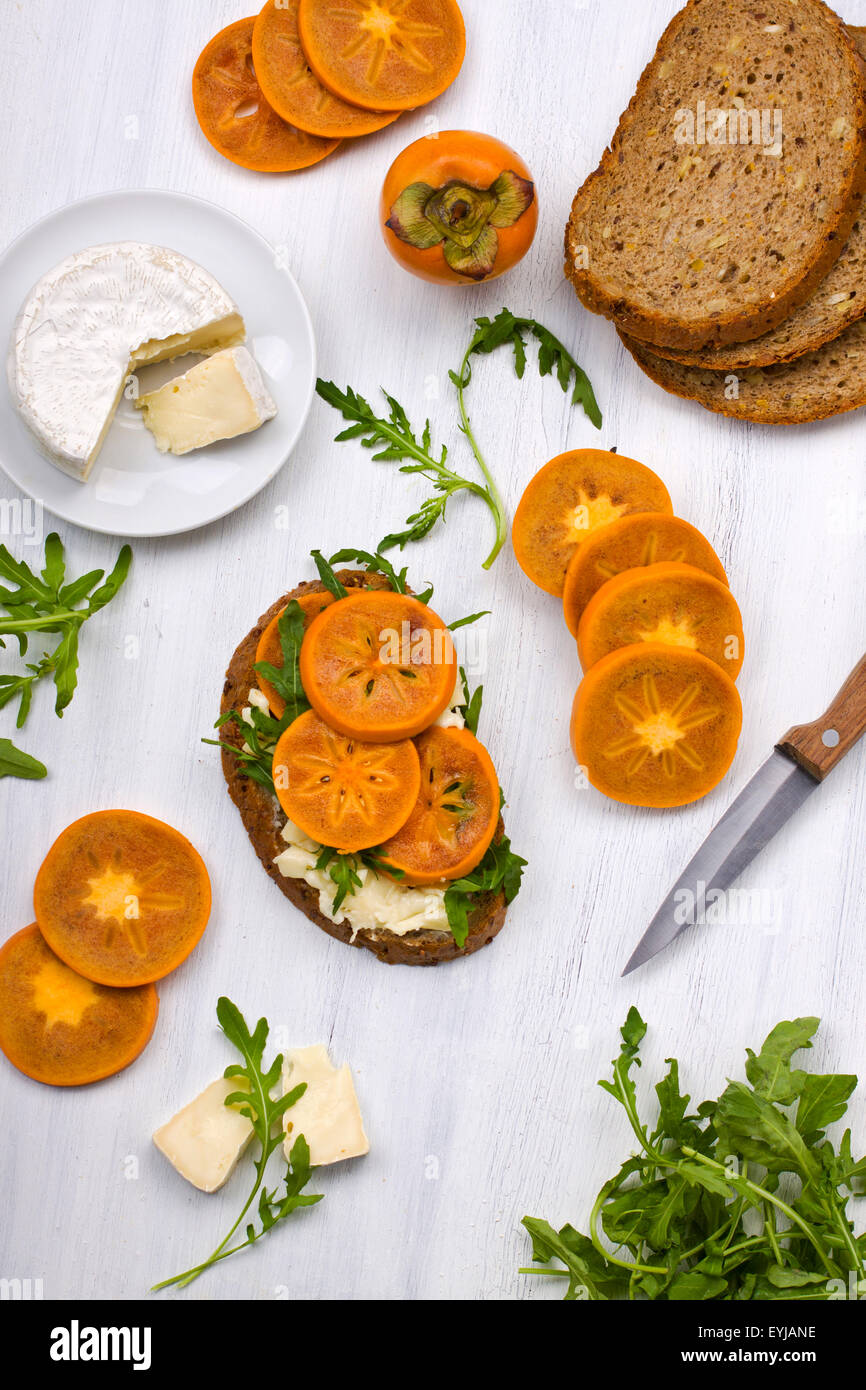Wholegrain sandwich with soft cheese and fresh ripe persimmon - Stock Image