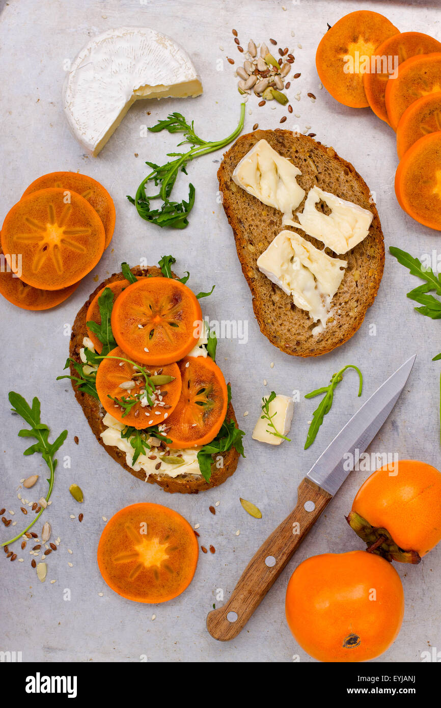 Sandwich with soft cheese, arugula and cut persimmon - Stock Image