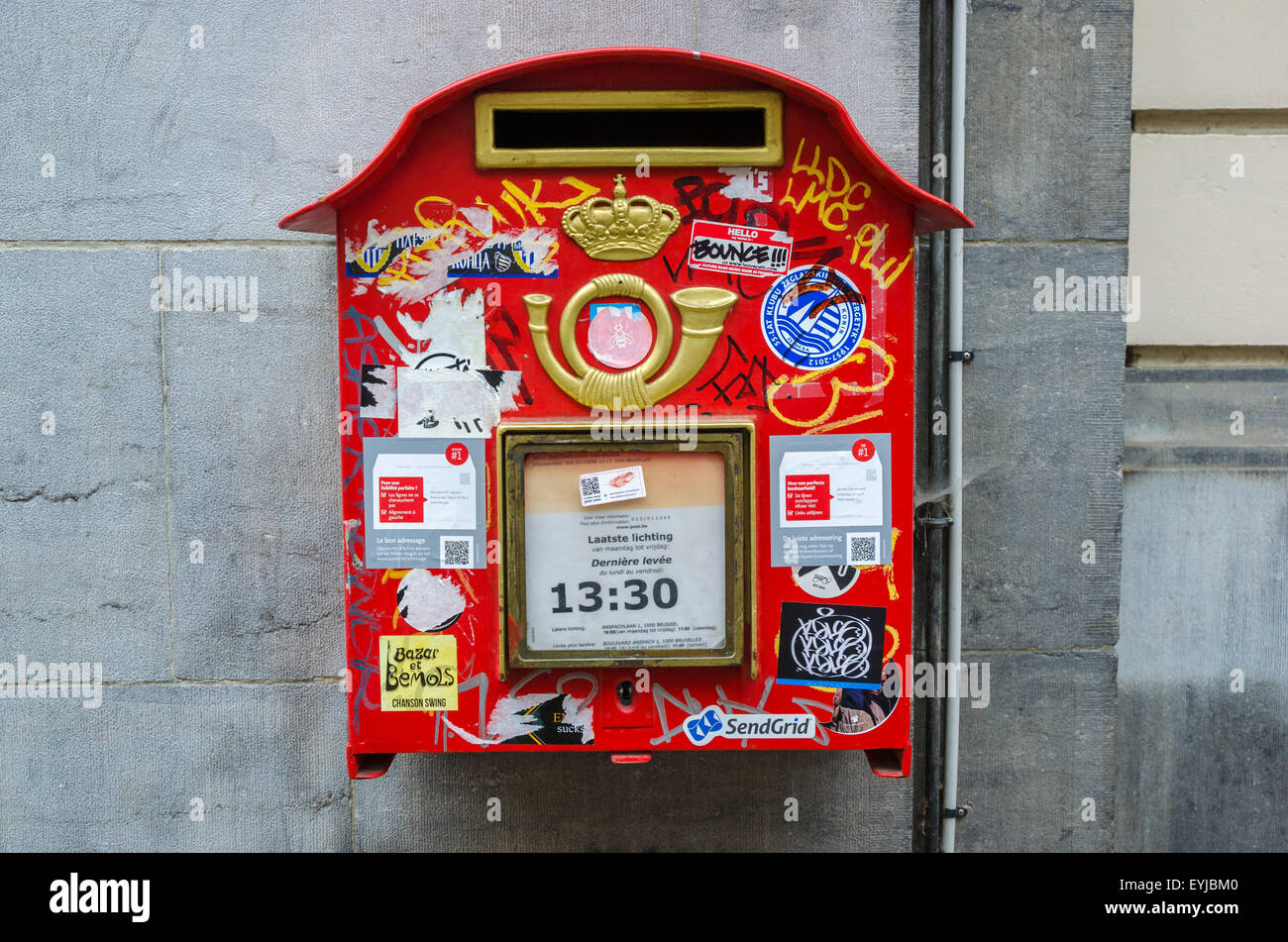 Belgian red mailbox on a wall, with many stickers. In Brussels. - Stock Image
