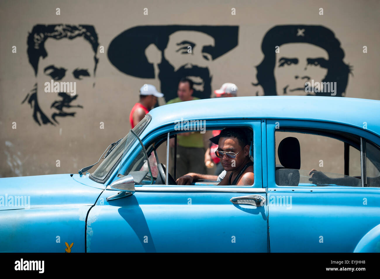 HAVANA, CUBA - JUNE, 2011: Pedestrians and classic American cars pass in front of stencil billboard featuring Communist - Stock Image