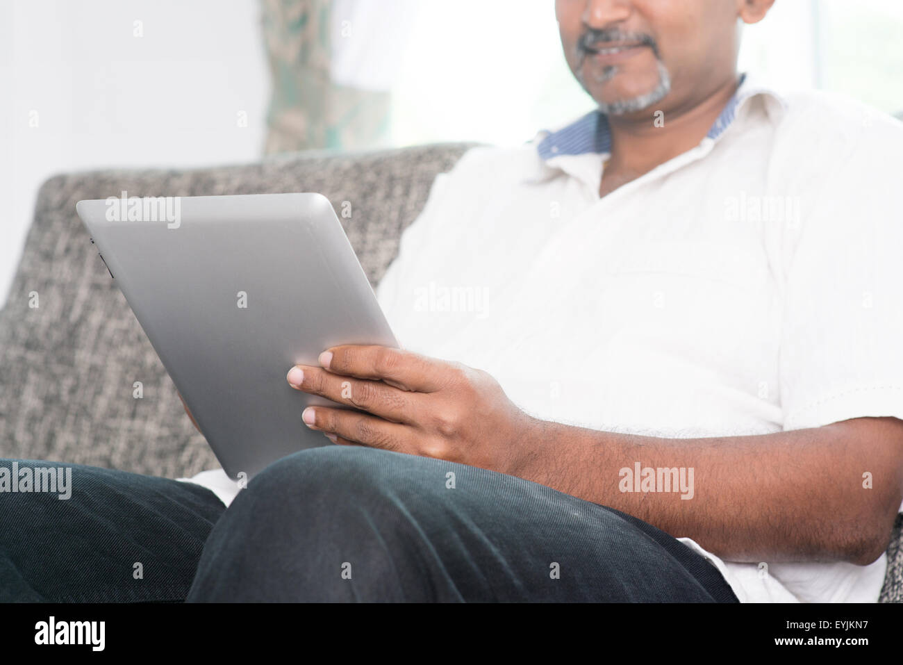 Modern technology concept. Mature Indian man using wireless touch screen digital tablet pc at home. Asian people - Stock Image
