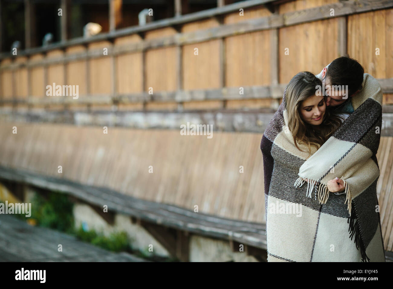 Young couple wrapped in plaid Stock Photo