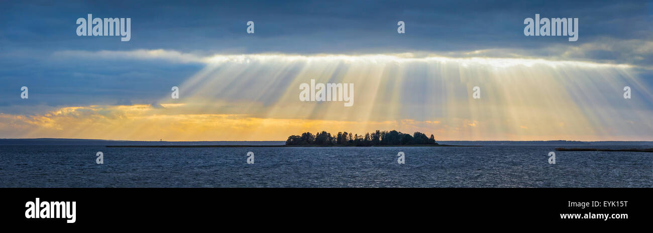 Panorama of lake sunset with sunrays coming through clouds. Lake Narach, Belarus - Stock Image