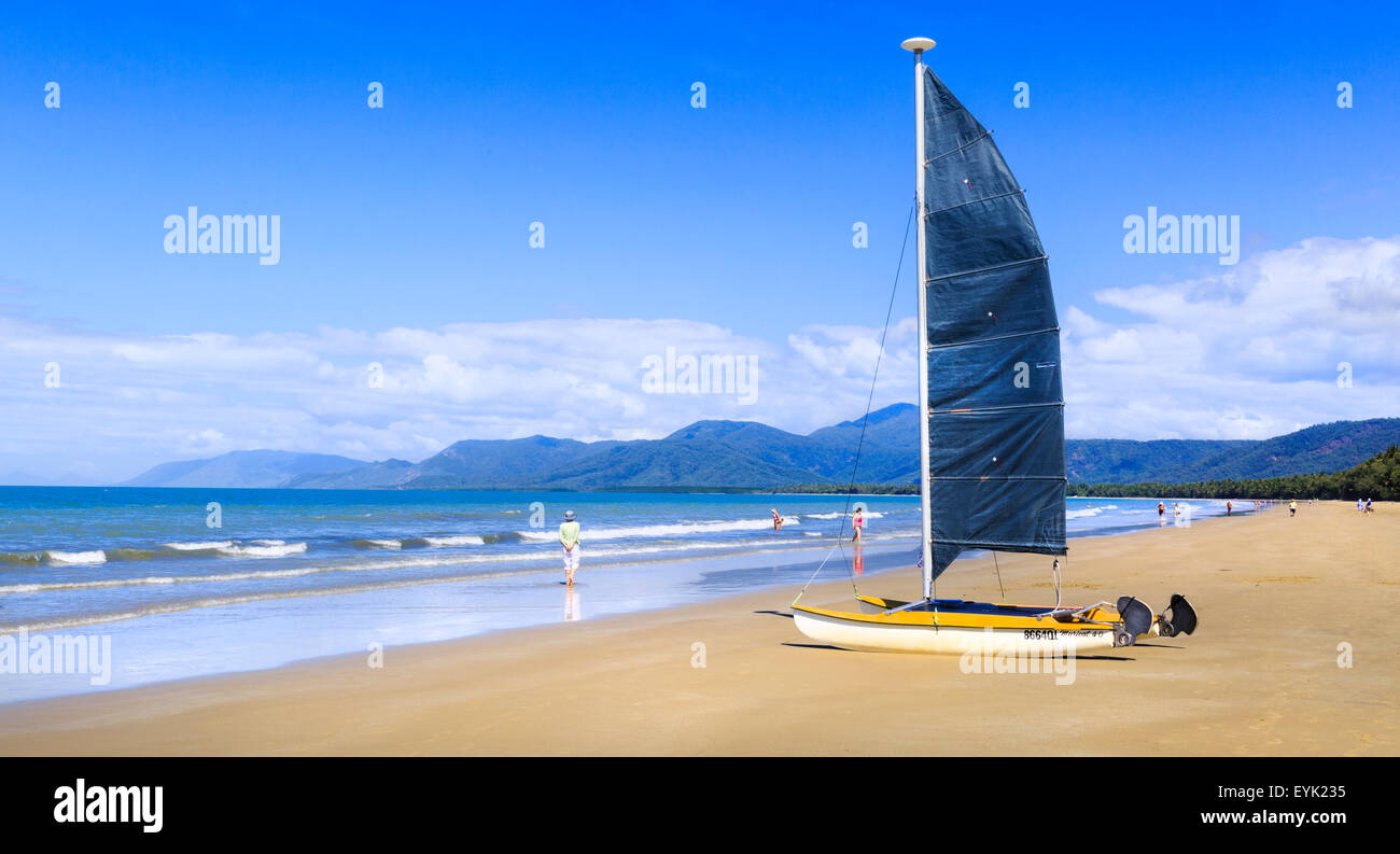 A catamaran sloop dinghy with a sail on the shores of Four Mile Beach in Port Douglas, Queensland, Australia - Stock Image