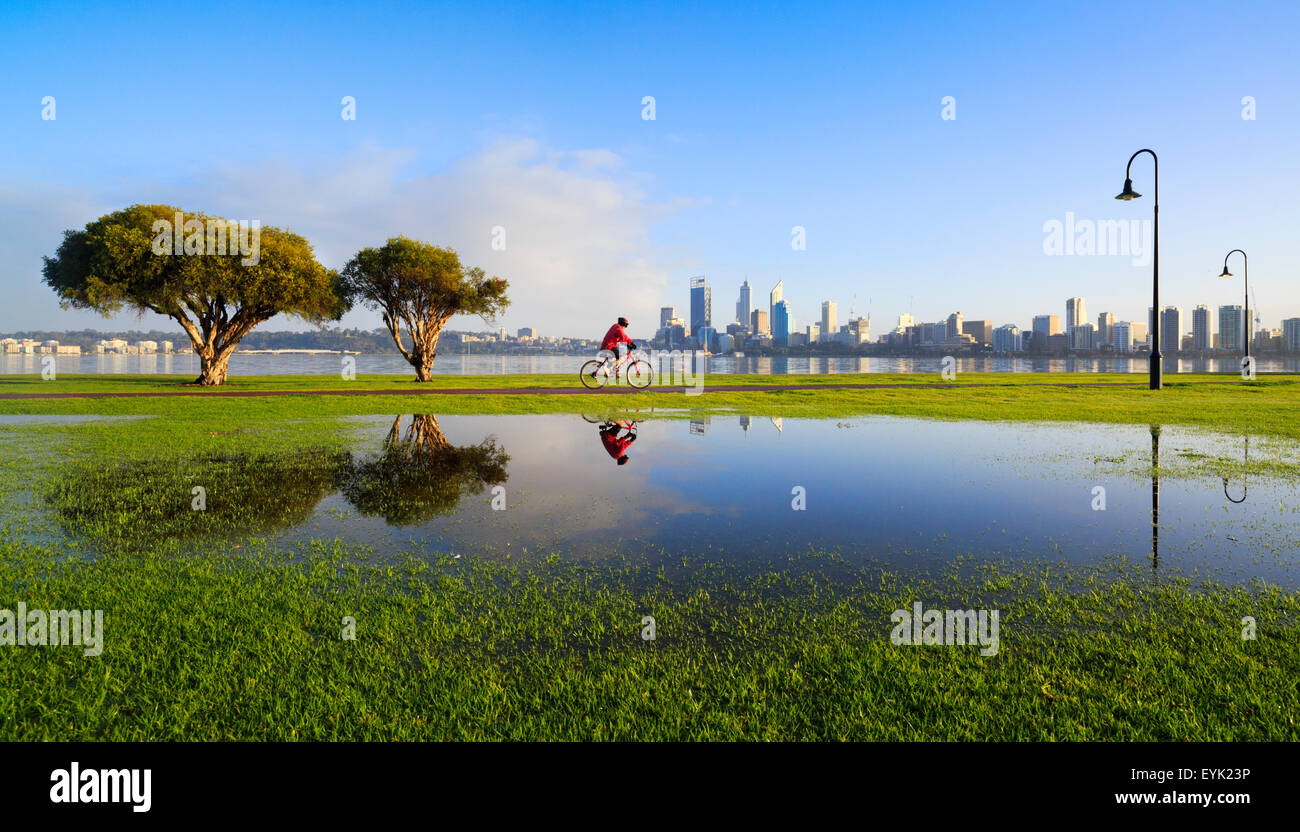 A man cycling along a cyclepath, reflected in a puddle with the city in the background.  Perth, Western Australia - Stock Image